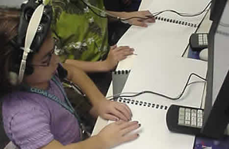Students in Mission Control reading braille scripts.