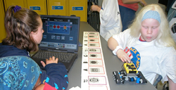 students programming a robot in the robotics lab.