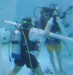 Wearing SCUBA gear, students build part of the space station truss system at the bottom of a 30 foot tank.